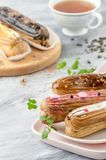 Pile Eclair with various fillings and a cup of tea on a light wo Royalty Free Stock Photos