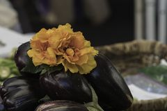 Pile of eggplant at the market decorated with a group of orange fabric flowers. Close up of a pile of eggplant Solanum melongena, or aubergine at the market Stock Photos