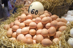 Pile of eggs. In straw basket at market Stock Photography