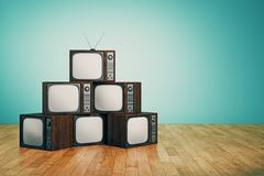 Empty retro TV pile. Pile of empty retro TVs in interior with blue wall and wooden floor. Creativity concept. 3D Rendering Stock Image