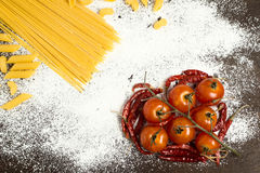 Pile en forme de coeur de poivrons rouges de tomate et de piment avec des macaronis Photographie stock libre de droits
