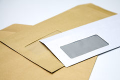 Pile of envelopes on white. Close up of pile of brown and white windowed envelopes on white background Stock Images