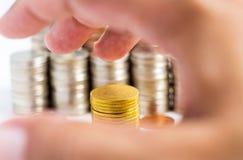 Pile et main d'or de pièces de monnaie sur la table blanche Photos libres de droits
