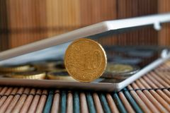 Pile of Euro coins in mirror reflect wallet lies on wooden bamboo table background Denomination is 10 euro cents. Pile of Euro coins in mirror reflect wallet Stock Photo