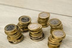 Pile of 1 Euro coins. Six piles of 1 euro coins on wooden floor in studio stock image