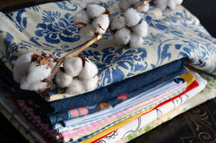 Pile of Fabrics and Cotton Plant Royalty Free Stock Photo