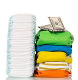 Pile fabrics, disposable diapers and money isolated on white. Royalty Free Stock Image
