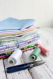Pile fabrics, scissors and thread on white table Royalty Free Stock Image