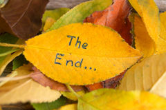 Pile of fallen colorful autumn leaves with inscription THE END royalty free stock photography