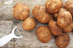 Pile of farm fresh potatoes with dirt and peeler Stock Photos