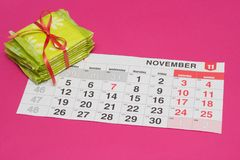 Pile with female pads and a calendar on a pink background, the frequency of menstruation, menstruation pads, pms royalty free stock image