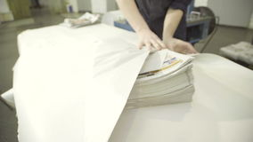 Pile of finished newspapers is wrapped in printing plant. stock footage