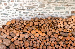 Pile of firewood against old stone wall Royalty Free Stock Images