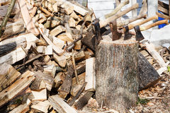 Pile of firewoods and several axes in wooden block Royalty Free Stock Images