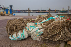 Pile of Fishing Nets on the Quay of a Fishing Harbor Stock Photos