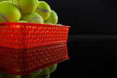 Pile of fluorescent yellow tennis balls in red plastic basket with reflection. Against black background Stock Photo