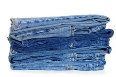Pile Of Folded Blue Jeans. Isolated Pile Of Folded Blue Jeans on white background Royalty Free Stock Photos