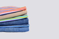 Pile of folded clothes. Pile of folded casual clothes on studio background with copy space Royalty Free Stock Photo