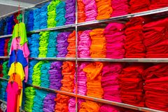 Pile of folded colourful t-shirts clothes in a shop. stock photos