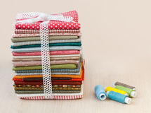 Pile of folded textile with spool of thread Stock Photo
