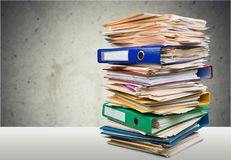 Pile of files in folders on white table. Pile folders files table yellow large white Stock Image