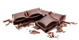 Pile foncée de barres de chocolat avec des miettes d'isolement sur un blanc Photos stock