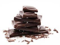 Pile foncée de barres de chocolat avec des miettes d'isolement sur un blanc image stock