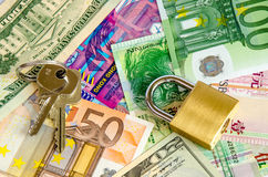 Pile of foreign currency banknotes with padlock and keys Stock Photography