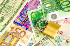 Pile of foreign currency banknotes with padlock Stock Image