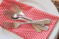 Pile of forks on napkin. A handful of forks rest on a red and pink polka dot napkin on top of a stack of white bistro plates Stock Images