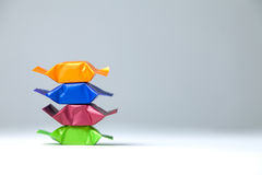 Pile of Four Colored Sweets. A pile of sweets in multicolored wrappers on a plain white and grey background Stock Photos