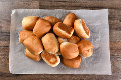 Pile Fresh Baked Dinner Rolls. Pile of fresh baked dinner rolls on a sheet of parchment paper. Top view in horizontal format stock image
