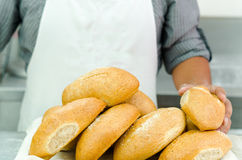 Pile of fresh bread loafs, baker standing behind with only apren and arms visible, bakery concept Royalty Free Stock Photos