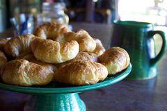 Pile of fresh croissants on green pottery cake stand. A batch of freshly baked croissants (pastries) is served on a green pottery cake stand on a wooden table Stock Image