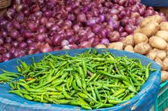 Pile of fresh green chili peppers, onions, potatoes on the market Royalty Free Stock Photos