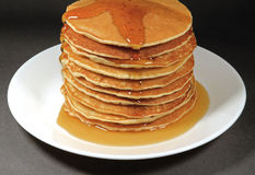 Pile of Fresh Homemade Pancakes Served with Maple Syrup on White Plate. On Black Background stock photography