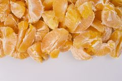 A pile of fresh peeled golden orange oranges on a white background, underneath a light background, an empty space for text. Stock Photography