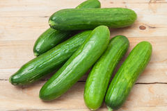 A pile of fresh picked cucumbers. On wooden background Royalty Free Stock Image