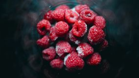 A pile of fresh raspberry berries quickly freeze in a glass. Healthy food. 4K timelapse stock video