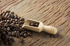 Fresh Raw Coffee Beans on Wooden Desk Table. Pile of Fresh Raw Coffee Beans on Wooden Desk Table with Wooden Spoon as Refresh Beverages Concept Royalty Free Stock Photos