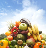Pile of fresh and tasty fruits and vegetables. The image is taken over the sky background Stock Photo