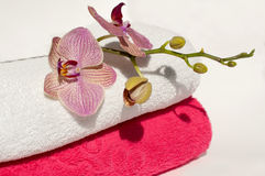 A pile of fresh towels with orchid flowers on them Stock Photo