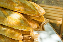 Pile of freshly baked rustic French baguettes on garden table, wooden chair, outdoor picnic preparation. Summer sunlight Stock Images