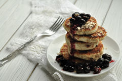 A pile of fried cheese pancakes with berries and a fork on a white linen napkin Royalty Free Stock Image