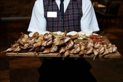 A pile of fried quails on a wooden board. In the hands of a waiter Royalty Free Stock Images