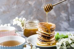 Pancakes with honey and tea for breakfast royalty free stock image