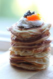 Pile of fritters at a window. Fritter with caviar and sour cream Royalty Free Stock Photography