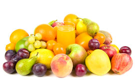 Pile of fruits around a glass of juice. Pile of colorful tasty fruits around a glass of juice Royalty Free Stock Photography