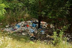 Garbage dump among trees and grass in the forest Stock Image
