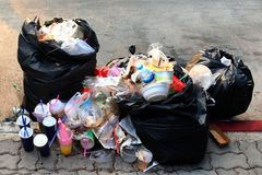 Pile of Garbage plastic black and trash bag waste many on the footpath, pollution trash, Plastic Waste and Bag Foam tray Garbage. The Pile of Garbage plastic royalty free stock photo